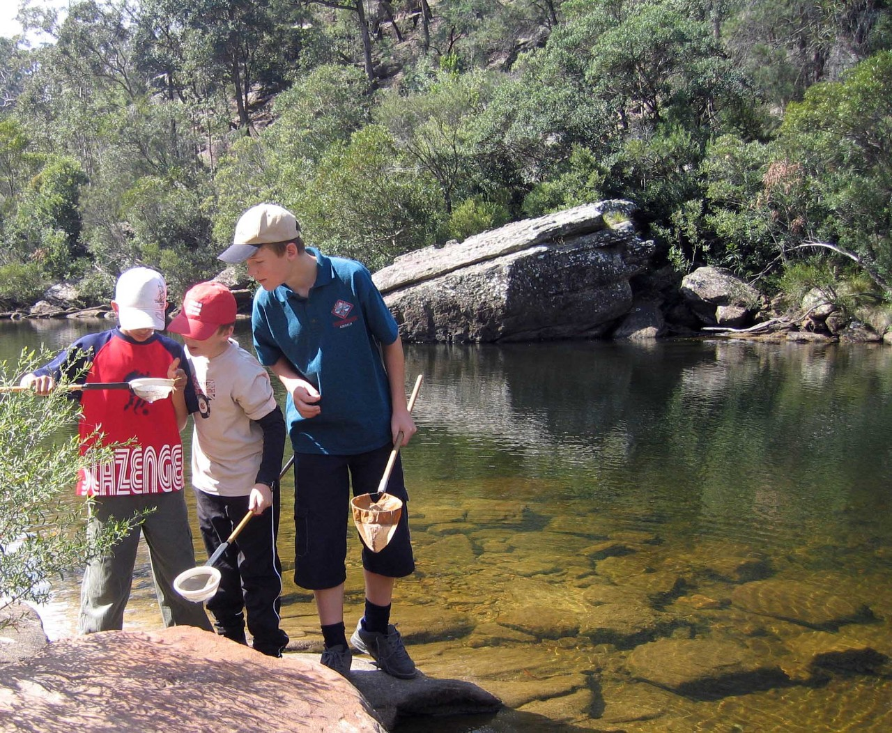 Students at a river bank learning how to dipnet.