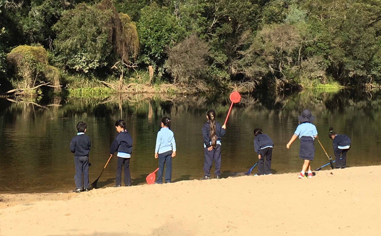 Students standing at the river bank at Simmo's Beach.